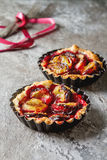 Homemade cake tartlets with plum on old stone background Royalty Free Stock Images