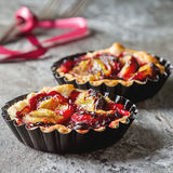 Homemade cake tartlets with plum on old stone background Royalty Free Stock Photo
