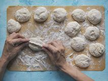 Homemade cakes of the dough in the women`s hands. The process of making pies with cabbage dough by hand. Homemade cakes of the dough in the women`s hands. The Stock Images