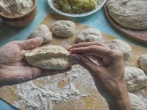 Homemade cakes of the dough in the women`s hands. The process of making pies with cabbage dough by hand. Homemade cakes of the dough in the women`s hands. The Royalty Free Stock Photo