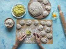 Homemade cakes of the dough in the women`s hands. The process of making pies with cabbage dough by hand. Homemade cakes of the dough in the women`s hands. The Royalty Free Stock Photography