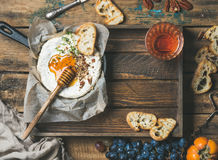 Homemade camembert with honey, glass of rose wine in tray. Homemade camembert cheese with honey and herbs in small pan, black grapes, persimmon, baguette slices Stock Image