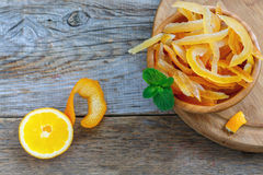 Homemade candied orange and lemon peels. Candied orange and lemon peels in a wooden bowl on old table Royalty Free Stock Image