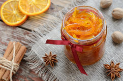 Homemade candied peels orange jam in glass jar. Homemade candied peels orange confiture in glass jar with spices - cinnamon, nutmeg and anise star on rusted Stock Images
