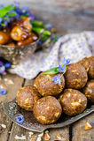 Homemade candies with dates and walnuts on vintage try and wooden background. East sweets for ramadan. Selective focus Stock Photos