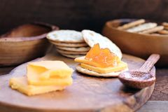 Homemade Cantaloupe Jam and Cheddar Cheese Appetizer. Water cracker, cheddar cheese and homemade Salted Vanilla Cantaloupe jam. Extreme shallow depth of field royalty free stock image