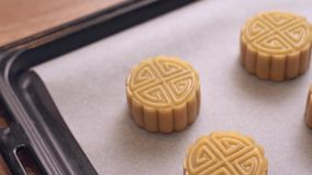 Homemade cantonese moon cake pastry on baking tray before baking for traditional festival. Homemade cantonese moon cake pastry on baking tray before baking for stock video footage