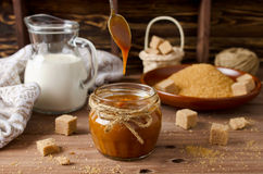 Homemade caramel sauce on wooden table Stock Image