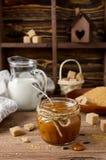 Homemade caramel sauce on wooden table Stock Photos