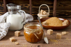 Homemade caramel sauce on wooden table Stock Images