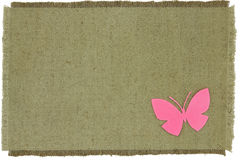 Homemade cardboard butterfly on green coarse cloth Royalty Free Stock Images