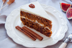 Homemade Carrot Cake. With pecans, butter cream on a white plate Stock Photos