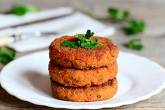 Homemade carrot cutlets on a plate. Delicious fried carrot cutlets with green onions and parsley. Healthy meatless cutlets recipe Royalty Free Stock Photos