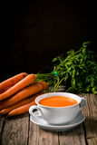 Homemade carrot soup with fresh ingredients. Bowl of delicious hot homemade carrot soup with fresh ingredients on a rustic wooden kitchen counter with copyspace stock photo