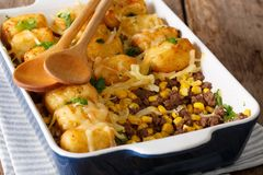 Homemade casserole of Tater Tots with minced beef, corn and chee. Se close-up in a baking dish on a table. horizontal Stock Image