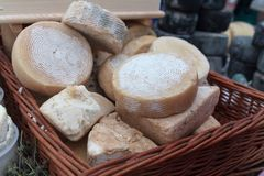 Homemade cheese in a basket on the market stall. Food stock photos