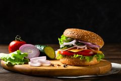Homemade cheese burger or hamburger with ham, tomatoes, cheese and lettuce on wooden board. Copy space. Fast food for breakfast or stock images