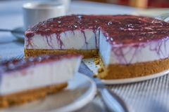 Homemade cheese cake with cranberry jam, served with a coffee royalty free stock photography