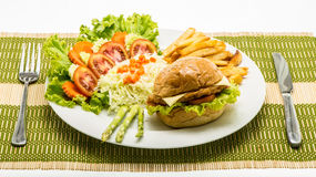 Homemade cheese chicken burger with fresh salad on plate. Royalty Free Stock Photos
