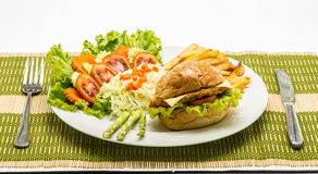 Homemade cheese chicken burger with fresh salad on plate. Stock Image