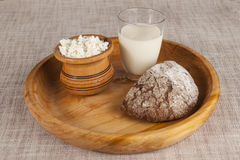 Homemade cheese, a glass of milk, brown bread on a wooden tray. Stock Photo