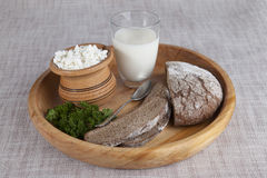 Homemade cheese, a glass of milk, brown bread on a wooden tray. Royalty Free Stock Photo