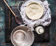 Homemade cheese making with cheesecloth , bottle of milk and wooden spoon on rustic background. Top view Royalty Free Stock Image