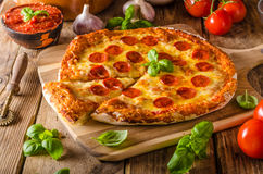 Homemade cheese pizza with salami. Delicious pizza with cheddar stock image