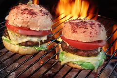 Homemade Cheeseburgers On The Hot Flaming BBQ Grill Royalty Free Stock Photography