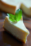 Homemade cheesecake with mint leaves. Piece of homemade cheesecake with mint leaves Stock Images