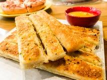 Homemade Cheesy Breadsticks. With Marinara Sauce for Dipping Stock Photo