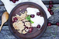 Homemade Cherry crumble. Wiht ice cream and cherries on an old wooden table background.Selective focus Stock Photography