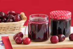 Homemade cherry jam in small glass jars. Fresh cherries on background. Homemade cherries jam and fresh cherries Stock Photos