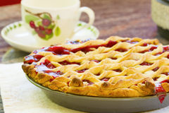 Homemade Cherry Pie. Cooling on a table with a tea cup in the background Royalty Free Stock Photos