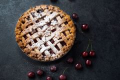 Homemade cherry pie with a flaky crust and powdered sugar royalty free stock photo
