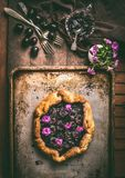 Homemade cherry pie or galette on aged baking tray and rustic kitchen table background with jam ,cutlery,and flowers, top view. Stock Image