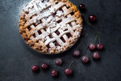 Homemade cherry pie with powdered sugar and fresh cherry royalty free stock image