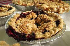 Homemade cherry pie traditional American dessert. Homemade cherry pie with assorted pies on a table at an outdoor market Royalty Free Stock Image