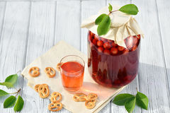 Homemade cherry preserved canned compote in glass with cookies on white wooden table in garden Royalty Free Stock Photo