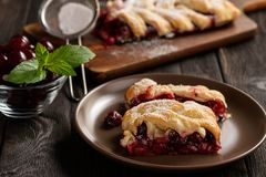 Homemade cherry puff pastry braid, on blue wooden background. Royalty Free Stock Image