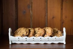 Homemade chewy choc-chip cookies in a decorative white dish on a. Wooden shelf royalty free stock image