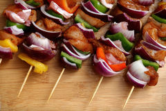 Homemade Chicken and Bacon Skewers Kebabs with Peppers Onions and Herb Marinate on wooden background. Homemade Chicken and Bacon Skewers Kebabs with Peppers Stock Images