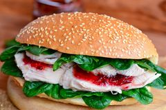 Boiled chicken breast, berry jam and fresh spinach burger. Simple and healthy chicken burger on a wooden board. Closeup royalty free stock photos