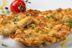 Homemade chicken breast schnitzel with herbs and one cherry toma. To on plate Stock Photography