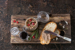 Homemade chicken liver pate. Glass jars of chicken liver pate with blackcurrant jam, pomegranate grain and sliced bread, served with vintage knife on wooden royalty free stock photos