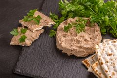 Homemade chicken liver pate with matzo and parsley. On black slate background. Horizontal view. Copy space stock photography