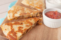 Homemade chicken mexican quesadilla on wooden. Chopping board with a side of salsa served in white bowl stock photos