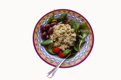 Homemade chicken salad served in a pretty bowl with spinach kalamata olives and cherry tomatoes - isolated on white. A Homemade chicken salad served in a pretty stock photo