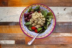 Homemade chicken salad served in a pretty bowl with spinach kalamata olives and cherry tomatoes - on rough wood table. A Homemade chicken salad served in a royalty free stock images