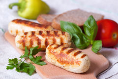 Homemade chicken sausages grilled on a wooden background. Homemade chicken sausages grilled on a wooden table Royalty Free Stock Photos